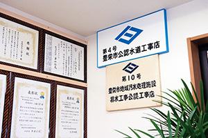 株式会社清水 賞状と共に壁に飾られている三協工業の市認定水道工事店(豊栄市当時)の看板